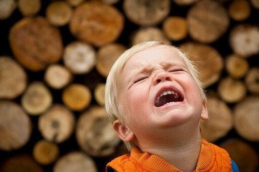 Płaczący chłopiec na tle drewnianej ściany