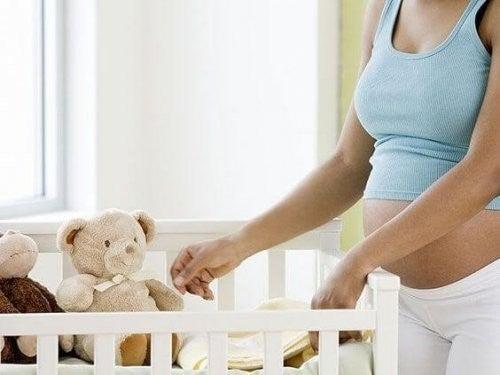 Matka w ciąży przygotowująca łóżeczko dla dziecka