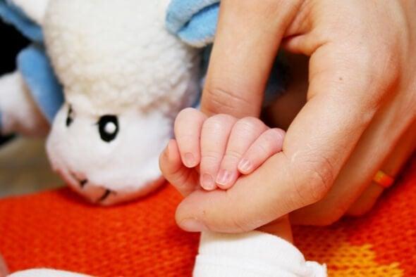 Ręka kobiety trzymająca rączkę dziecka