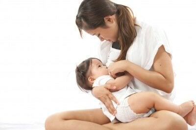 Siedząca mama karmiąca dziecko piersią - karmienie piersią po cięciu cesarskim