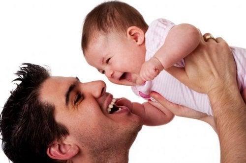Śmiejący się tata unoszący na rękach roześmiane dziecko