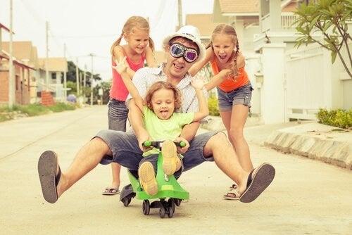 Tata bawiący się na dworze z trójką dzieci