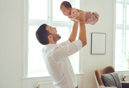 Tata podnoszący niemowlę na rękach