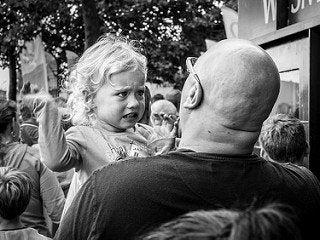 Tata trzymający na rękach skrzywioną dziewczynkę