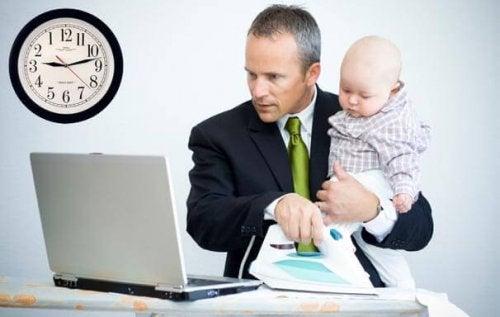 Tata w garniturze pracujący na komputerze z dzieckiem na rękach