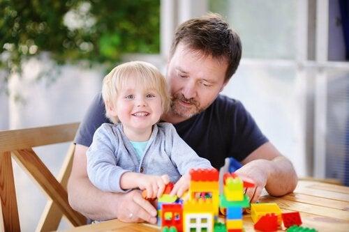 Tata z dzieckiem układający klocki LEGO na stole