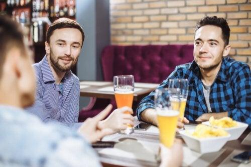 Trzech mężczyzn siedzących przy stoliku w barze i pijących piwo