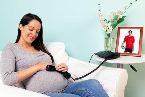 Uśmiechnięta mama trzyma telefon przy brzuchu, aby dziecko było szczęśliwe przed narodzinami
