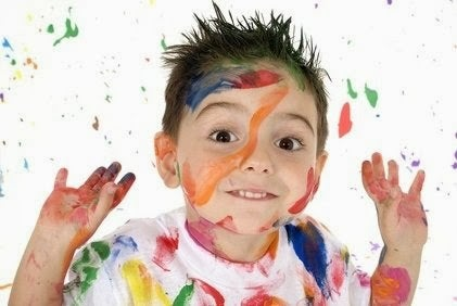 Uśmiechnięty chłopiec pomazany kolorowymi farbami
