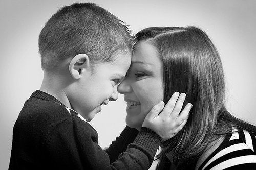 Uśmiechnięty chłopiec przyciskający czoło do czoła mamy