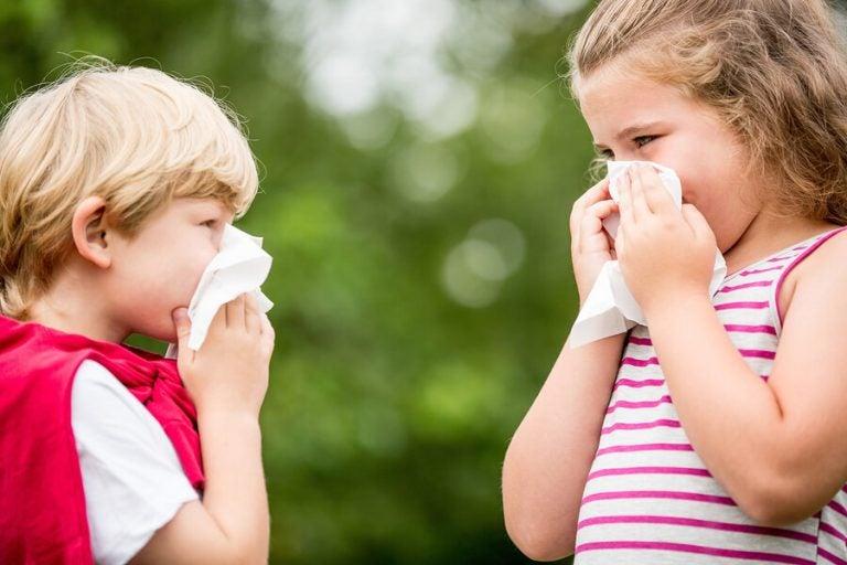 Chłopiec i dziewczynka dmuchający nosy w chusteczki