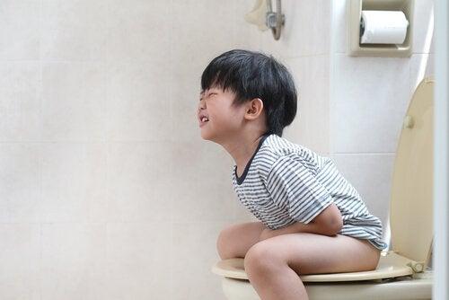 Chłopiec siedzący na toalecie, trzymający się za brzuch