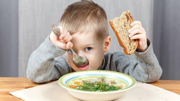 Chłopiec siedzący przy stole, jedzący zupę i trzymający kromkę chleba w ręku