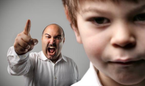 Chłopiec w tle krzyczący na niego tata - tak zachowują się toksyczni rodzice
