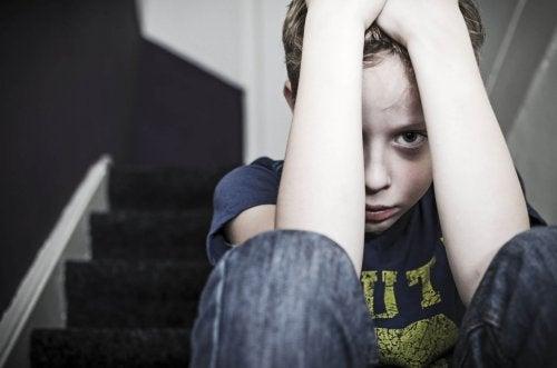Chłopiec z podbitym okiem chowający głowę w dłoniach - bicie dzieci i kara cielesna
