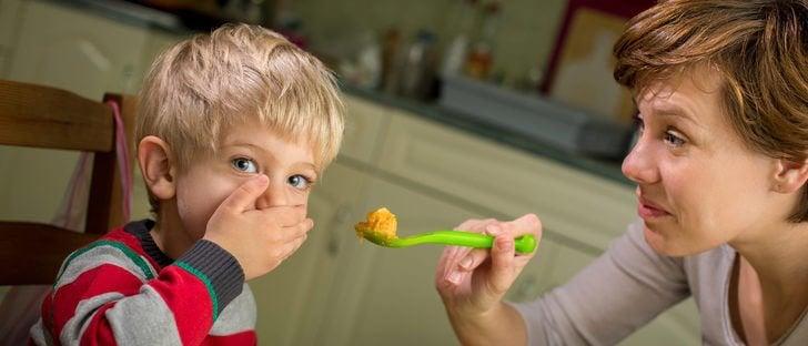 Chłopiec zasłaniający usta ręką i mama trzymająca przed nim łyżkę z jedzieniem