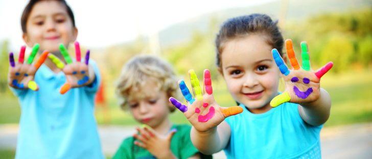 Dwie dziewczynki i chłopiec wyciągający przed siebie ręce z kolorowymi palcami