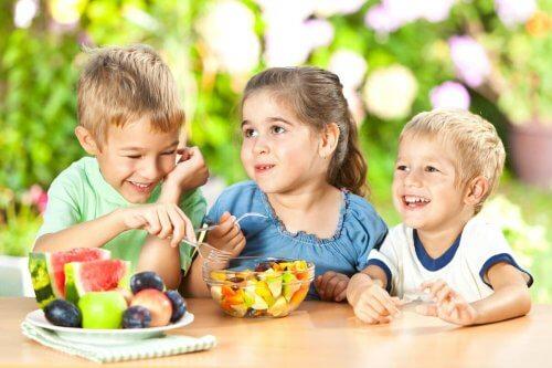 Dwóch chłopców i dziewczynka siedzący przy stole i jedzący zdrowe przekąski dla dzieci - owoce z miski