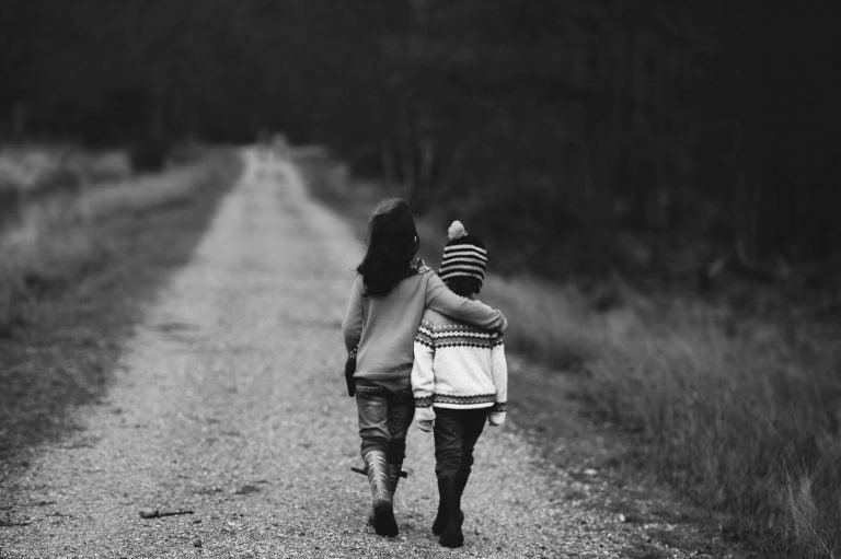 Dwoje przytulonych dzieci idących razem drogą