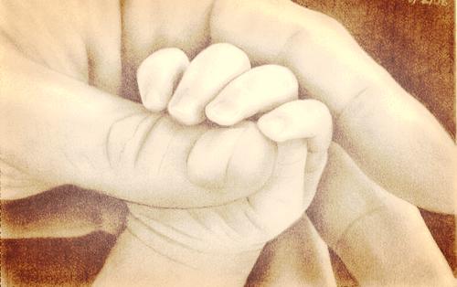Małe dziecko łapiące za palec rodzica
