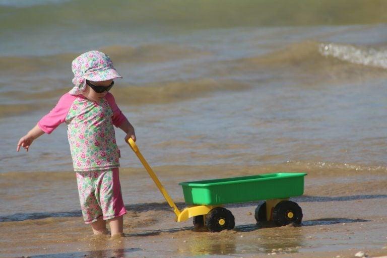 Dziecko ciągnące wózek po brzegu morza