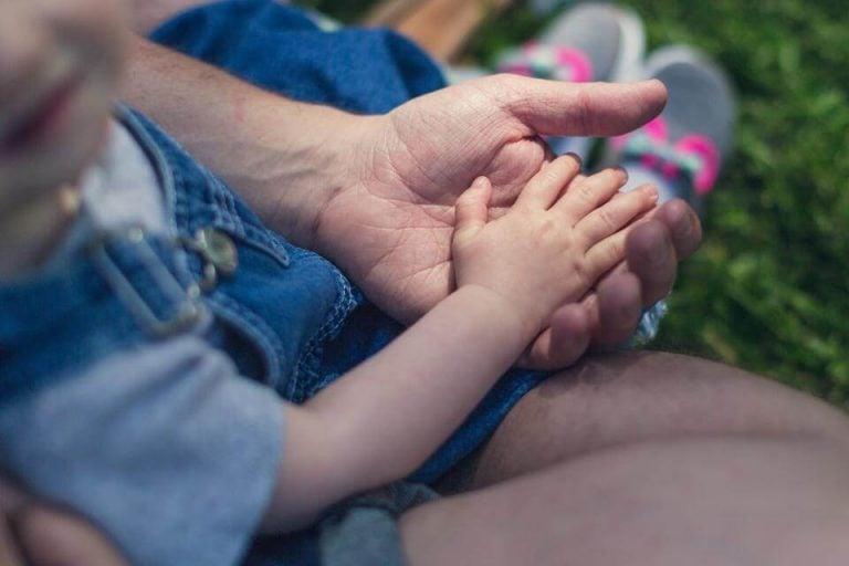Dziecko kładące dłoń w dłoni taty