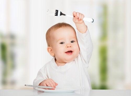 Dziecko siedzące przy stole, podnoszące do góry rękę z widelcem