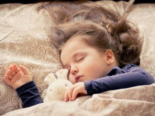 Dziewczynka śpiąca z pluszowym króliczkiem