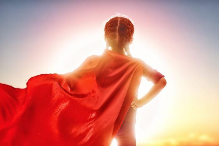 Dziewczynka stojąca w bohaterskiej pozie na tle słońca z powiewającą peleryną