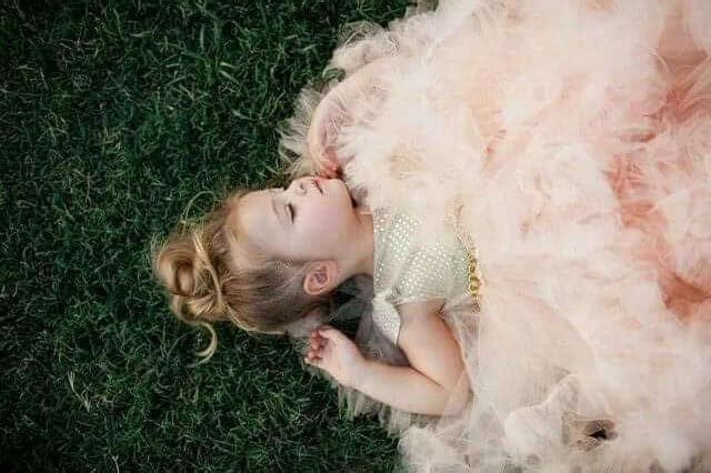 Dziewczynka w tiulowej sukience leżąca na trawie