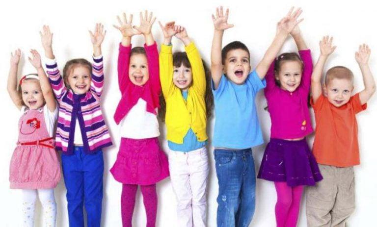 Grupa śmiejących się dzieci stojąca w rzędzie z rękoma wyciągniętymi do góry - ćwiczenia uczące czym jest świadomość emocjonalna