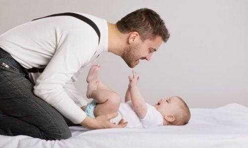 Jak łaskotać i całować dziecko po brzuchu - tata bawi się z niemowlęciem