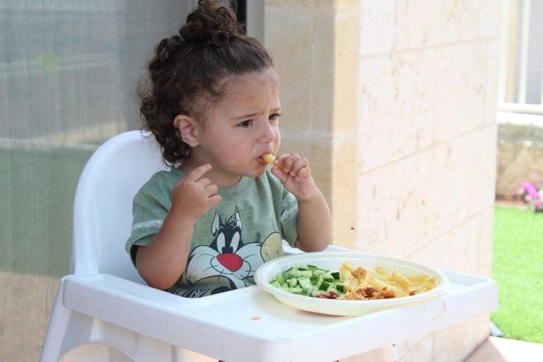 Jedząca dziewczynka siedząca na krześle do karmienia, próbująca najlepsze pokarmy dla dziecka