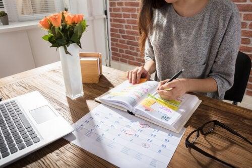 Kobieta siedząca przy stole, tworząca grafik w kalendarzu
