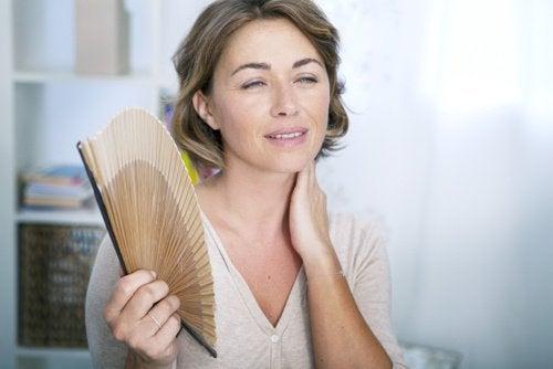 Kobieta trzymająca rozłożony wachlarz w dłoni - objawy menopauzy i uderzenia gorąca