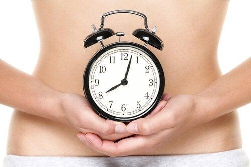 Kobieta trzymająca zegarek na tle brzucha