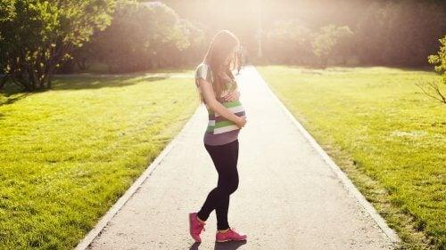 Kobieta w ciąży obejmująca brzuch na ścieżce w parku