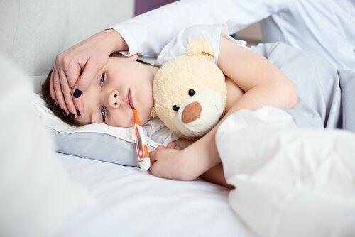 Leżący na boku chłopiec z termometrem w ustach i mama przykładająca mu rękę do czoła
