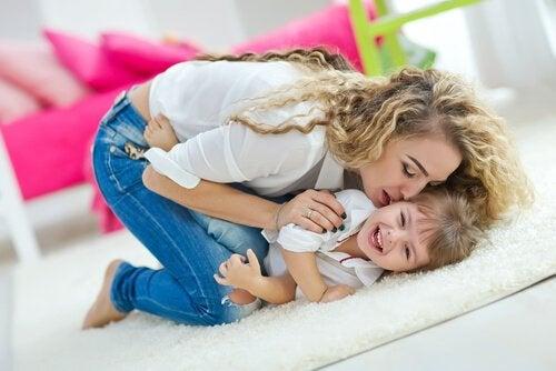 Mama całująca roześmianą córkę leżącą na dywanie w salonie - wychowanie szczęśliwego dziecka