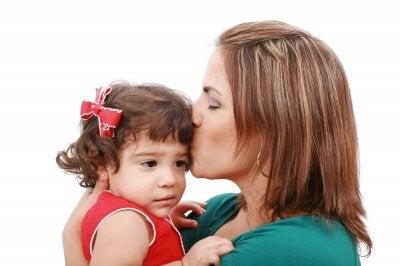 Mama całująca trzymaną na rękach córkę w czoło