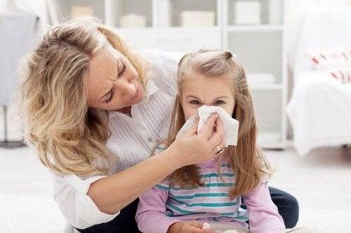 Mama pomagająca córce dmuchać nos w chusteczkę