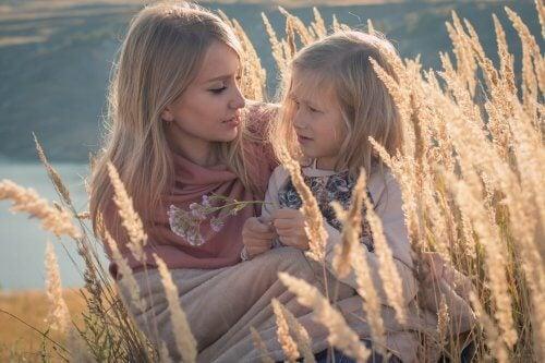Mama rozmawiająca z córką siedząc w łanie zboża
