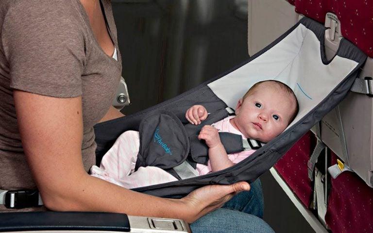 Mama trzymająca dziecko w podróżnym nosidełku