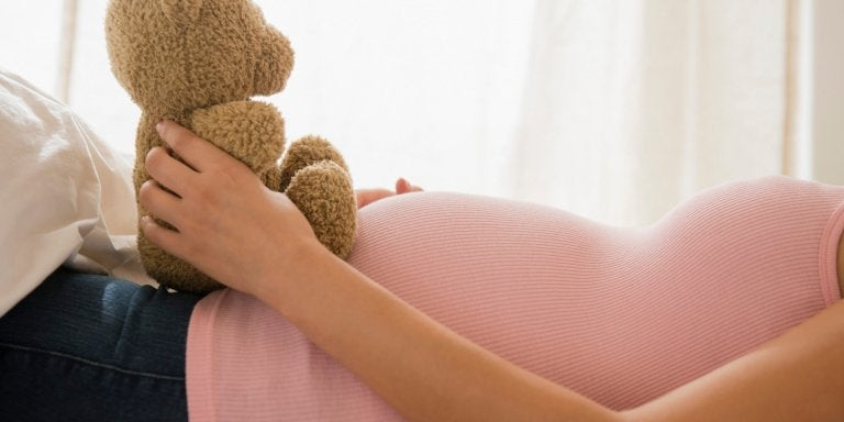 Mama trzymająca pluszowego misia na brzuchu w ciąży - w którym tygodniu ciąży jesteś?