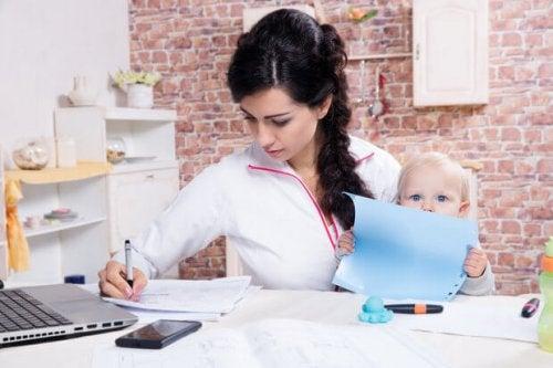 Mama przy stole z córką na kolanach, pisząca pracę - macierzyństwo i studiowanie