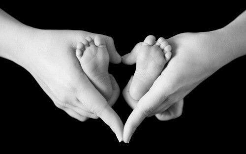 Mama trzyma w rękach stopy dziecka