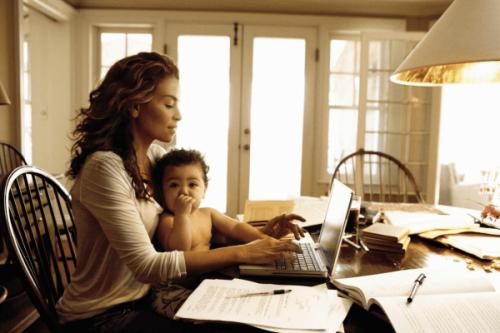 Matka pracuje przy biurku z synem na kolanach