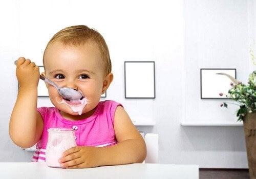 Niemowlę jedzące łyżką jogurt ze słoiczka z zabrudzoną twarzą