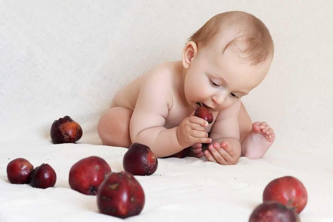 Niemowlę leżące między jabłkami, wkładające jedno jabłko do ust