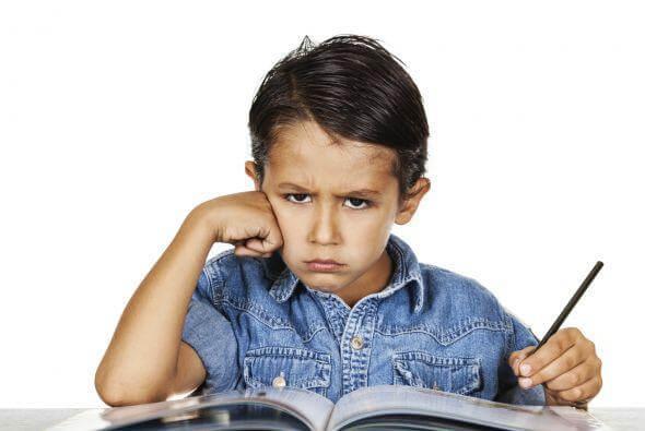 Obrażony chłopiec siedzący z ołówkiem w ręku nad książką